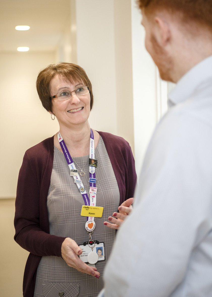 Karen is in a corridor smiling and talking to another member of staff.
