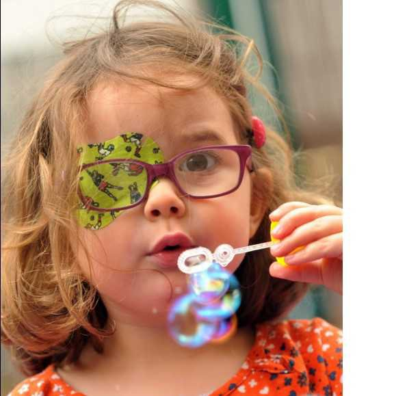 An ophthalmology paediatric patient blowing some bubbles