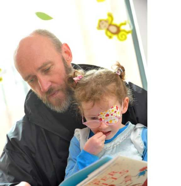 A father with his daughter who is an ophthalmology patient and they are reading together