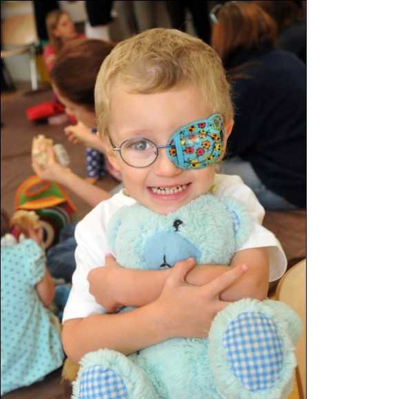 An ophthalmology paediatric patient hugging his bear
