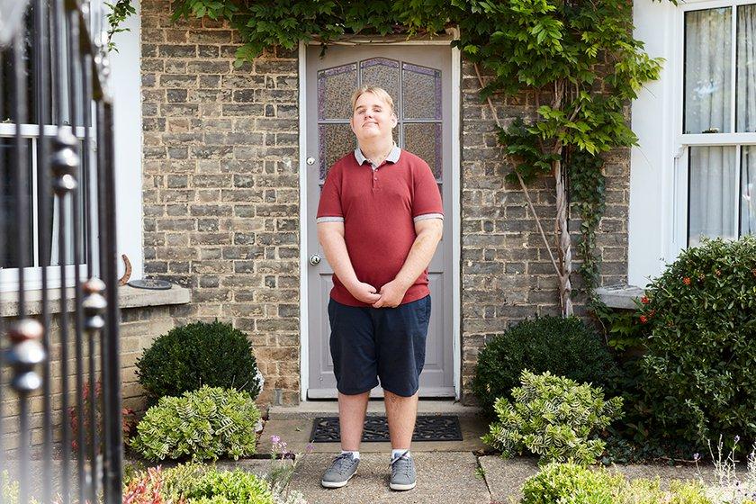 Alex posing outdoor outside of his front door
