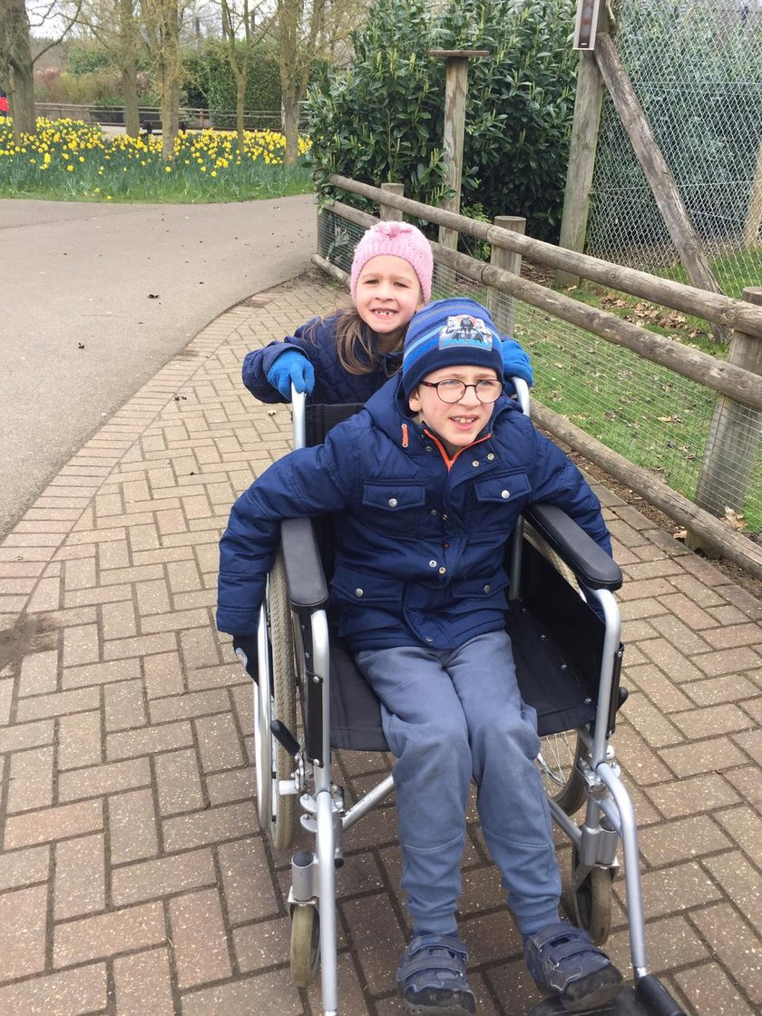 Alex in a wheelchair with his sister