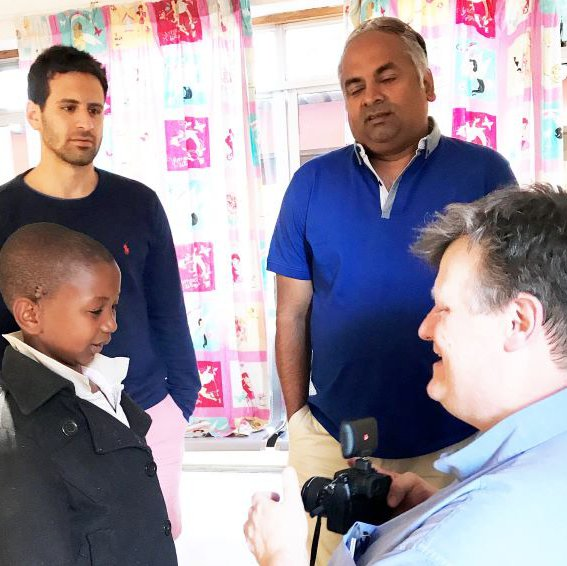 CGHP volunteer surgeon Julian Fraser, now retired, shows his camera to the same young patient. Watching on are Consultant Surgeon, Mr Vijay Santhanam (back right), and trainee surgeon Shadi Basyuni (back left)