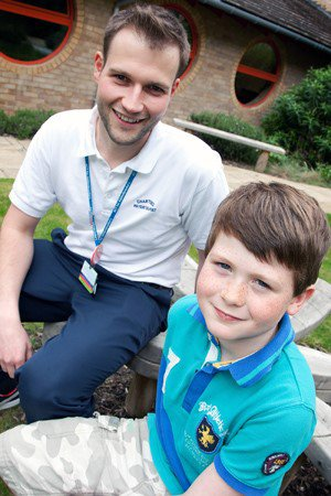 A smiling paediatric physiotherapist with a smiling child outside