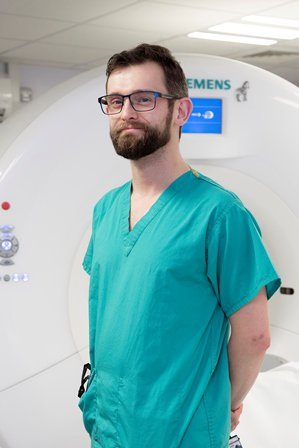 Chris is wearing green scrubs, he is standing up with his hands behind his back, smiling at the camera.