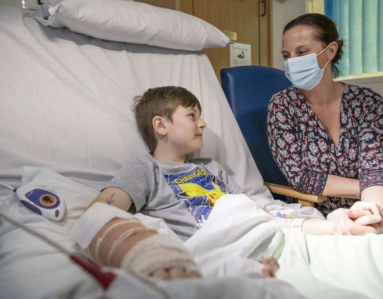 Boy in hospital bed being comforted by his mum