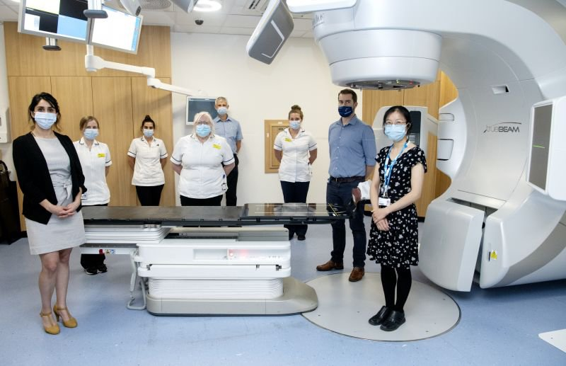 The radiotherapy team with June Dean and Tara Djanani from BrainLab standing in front of the new equipment that enables delivery of precision radiosurgery and radiotherapy to patients with cancer