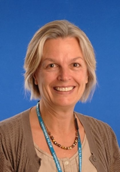 Headshot of Dr Helen Firth smiling at the camera in front of a blue backdrop.