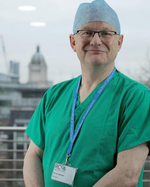 Doctor Liam Brennan is looking smiling at the camera. He with wearing an operating theatre cap, green scrubs and a blue lanyard.