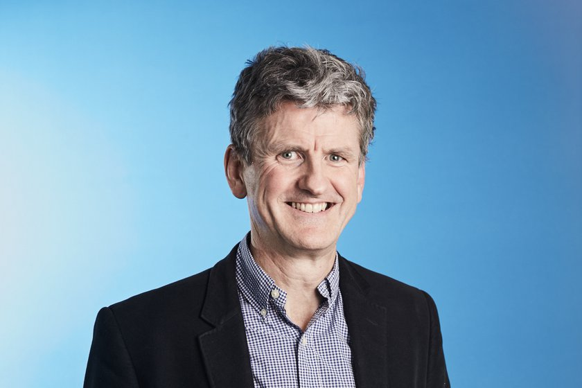 A headshot of Dr Parkes smiling at the camera against a blue background
