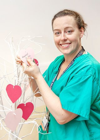 Elanie Jack is smiling at the camera whilst wearing scrubs and decorating a white tree by hanging paper hearts on it.