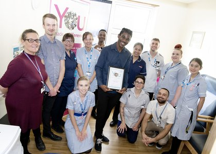 Elliot with his team holding his You made a difference certificate