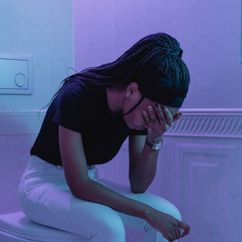 A girl sitting in a bathroom looking concerned