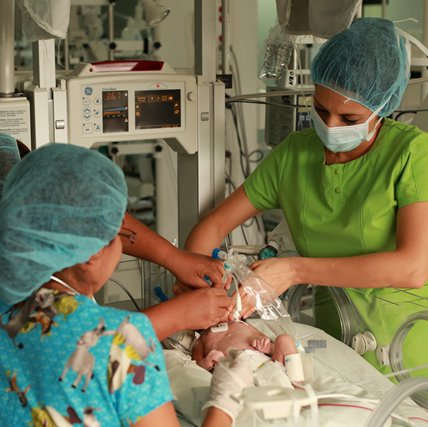 Three nurses are around a bed care for a baby