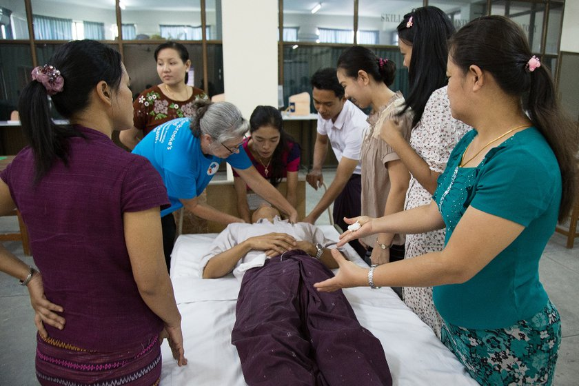 A group of trainee nurses are surrounding a patient while a member of Cambridge Global Health Partnership demonstrates an element of care.