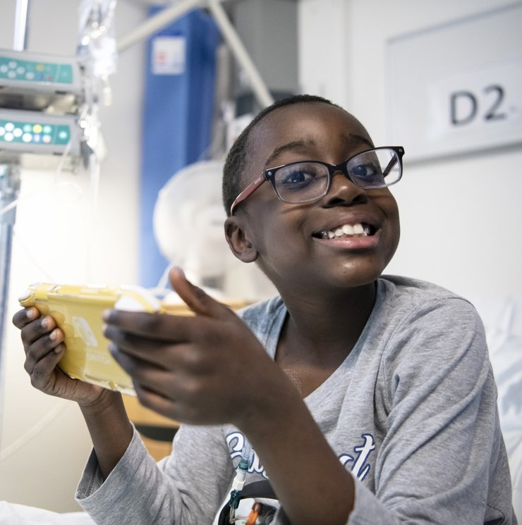 A boy using technology in a hospital bed