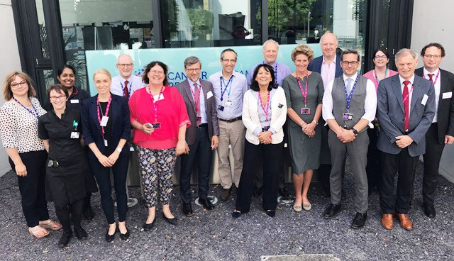 OECI assessors and some of the research and clinical staff are all stood together in a group outside the CRUK building smiling at the camera.