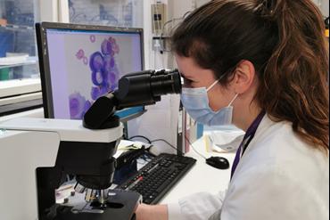 Hannah Creasey at work, looking into a microscope