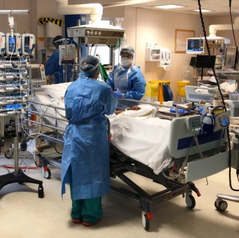 Shot of two staff members in full PPE in the critical care unit standing around a bed with a patient caring from him