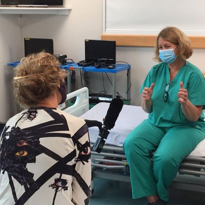 Dr Rowan Burnstein explains about the MDT Covid clinic to Emily Morgan, health editor, ITN