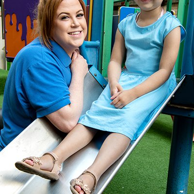 Jade Allard is wearing a blue t-shirt smiling at the camera she is next to a slide who has a young patient sat on it also smiling at the camera.