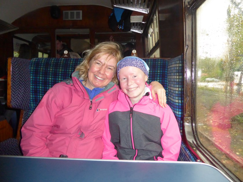 Anita with her daughter Jess on a train. They are both smiling.
