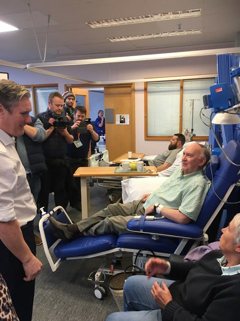 Keir Starmer is talking to patients at Addenbrooke's and is surrounded by photographers and interviewers.