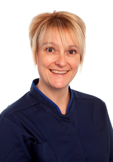 Lorraine Szeremeta is wearing her nurse uniform and is smiling at the camera and is against a white background.