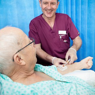 Martin Fabb is smiling and caring for a patient. The patient is lying in a hospital bed speaking to Martin has he gives them an injection.