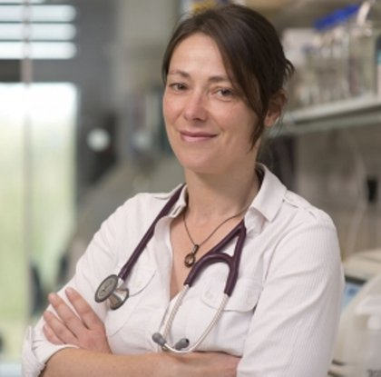 A headshot of Professor Menna Clatworthy smiling at the camera with her arms crossed with a hospital setting in the background.