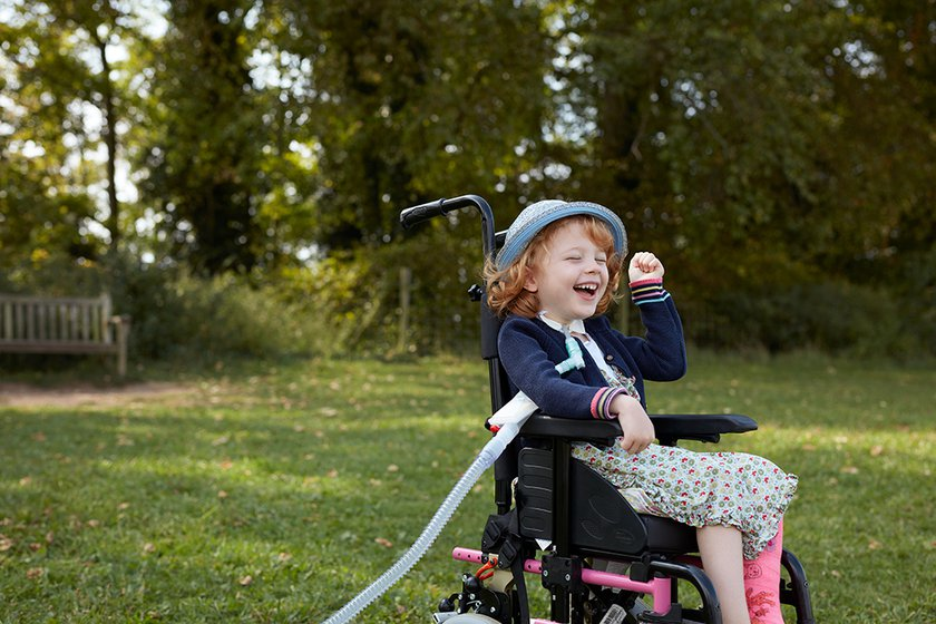 Phoebe outside in a garden on a wheelchair