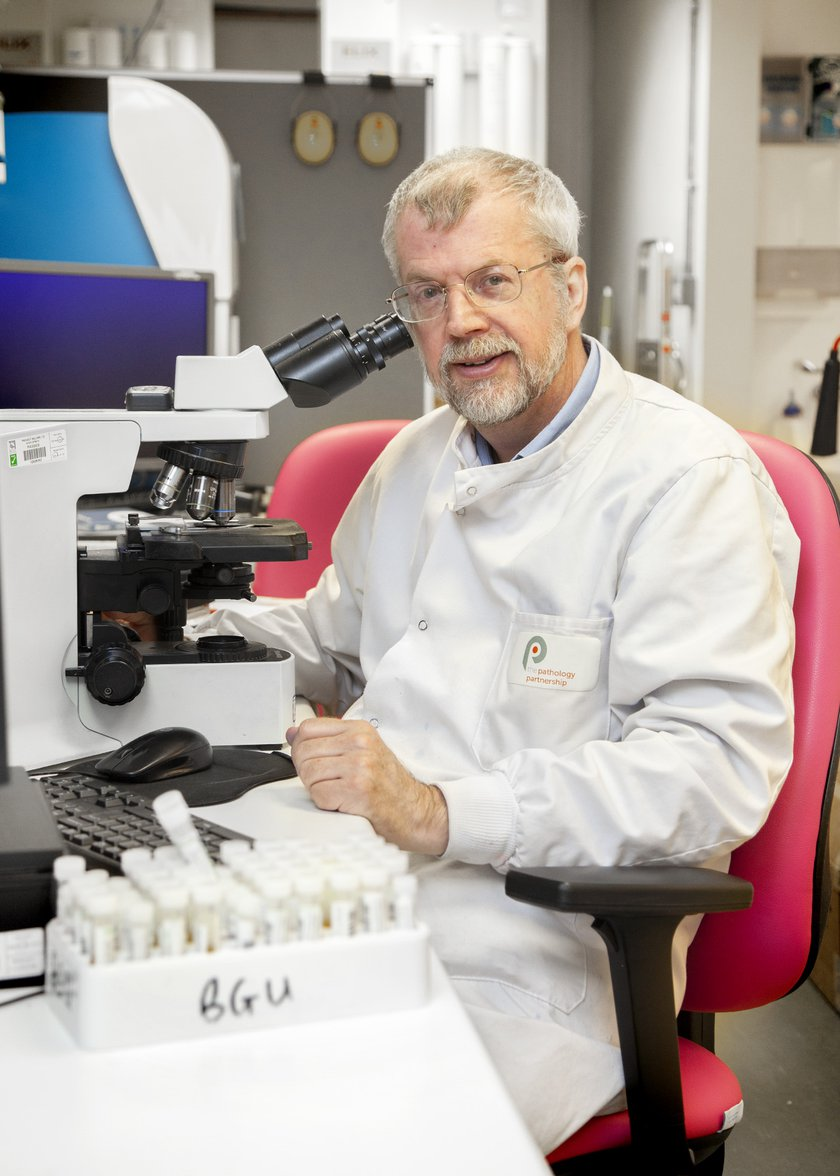 Rod Lynn is sat down in front of a microscope wearing lab protective clothing and is smiling at the camera