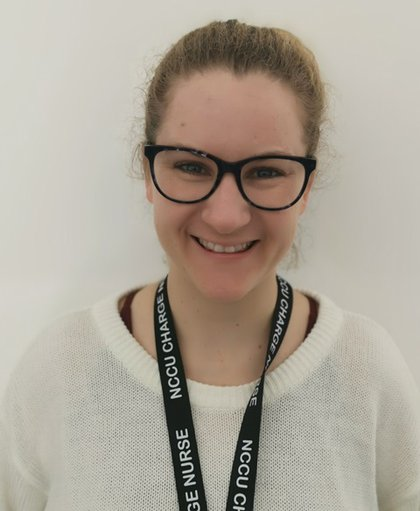 Headshot of Rosie Tasker smiling at the camera she is wearing black rimmed glasses, a white jumper and a NICU lanyard