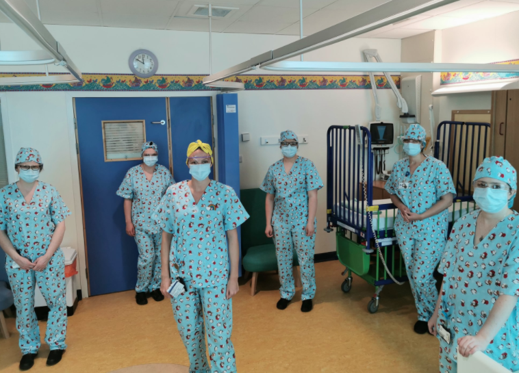 Six members of staff are all wearing matching handmade penguin scrubs standing up and looking at the camera in a hospital ward.