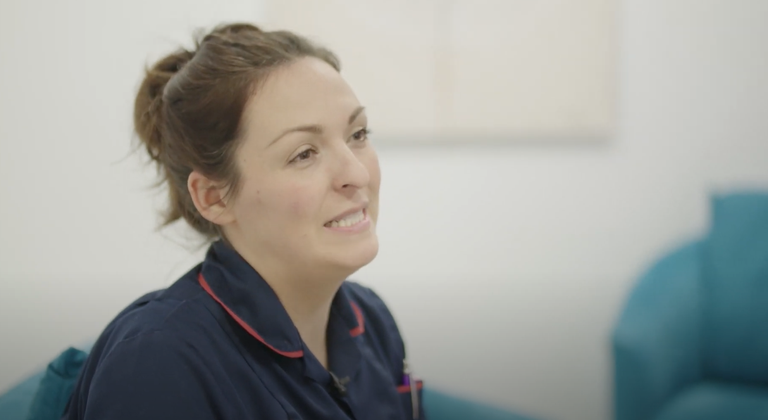 Rosie - Teenage Cancer Trust specialist nurse is smiling towards the right hand side of the screen. Shoulders up, she is wearing a blue nurses uniform.