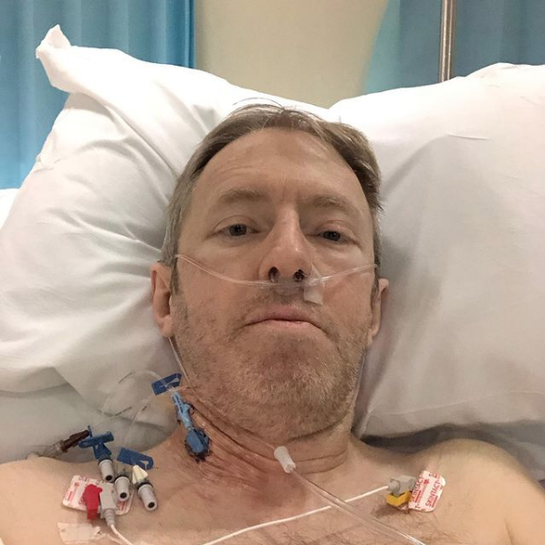 A man is sitting in a hospital bed.
