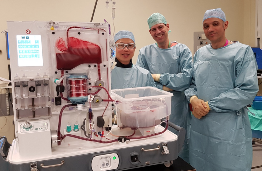 Three men stand facing the camera behind a liver perfusion machine.
