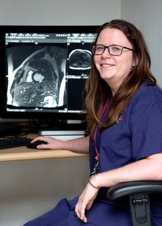 Sharon is sat down by a computer looking at medical scans and smiling at the camera.