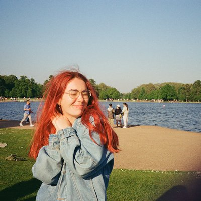 Sky stands in the sunshine, long red hair, with a big smile and arms spread out wide