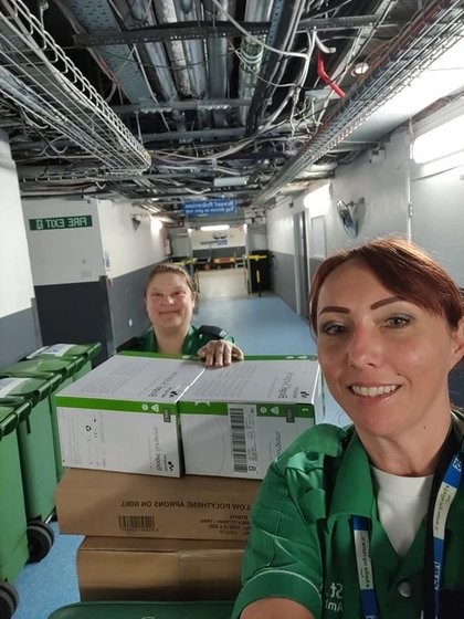 Selfie of two St John ambulance volunteers smiling at the camera transport boxes of supplies through the hospital