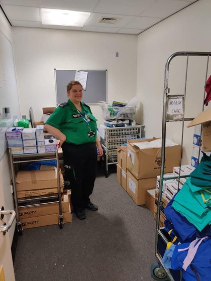 A St John ambulance volunteer smiling at the camera in a room at the hospital with PPE supplies