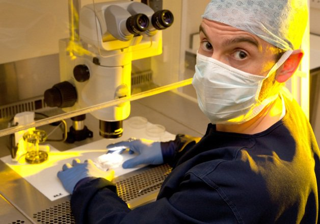 Stephen Harbottle is in a lab setting with a microscope. He is wearing gloves, mask and a medical cap and looking at the camera.