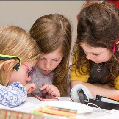 Children wearing new listening glue ear headphones - landscape