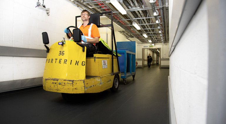 A member of the Estates team driver a tug which are used on Level 1 to transport equipment underneath the corridors of the hospitals