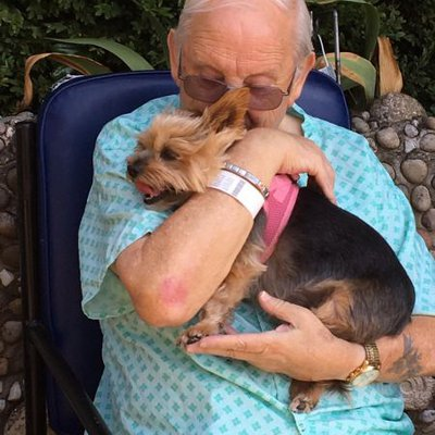 Ron sitting in a wheelchair in the hospitals' garden, holding Misty and rejoicing to be reunited with her