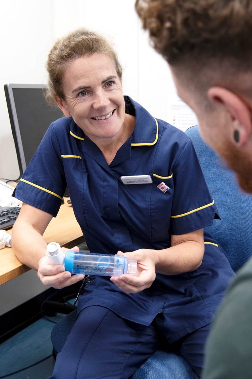 Caroline Owen is smiling at a patient and showing them how to use an inhaler device.
