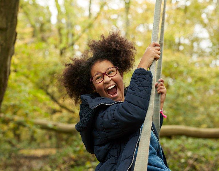 Zofeya swinging on a tree