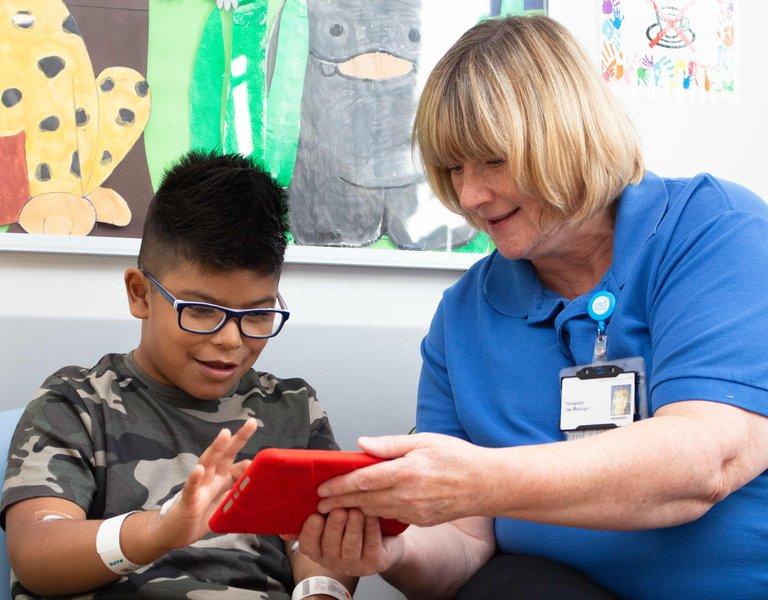 Boy playing on ipad accompanied by hospital staff