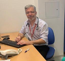 Headshot of Dr Richard Biram sitting at his desk in a consultation room