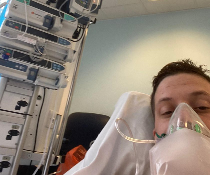 David Eggerton is lying in a hospital bed connected to a ventilator and looking at the camera.